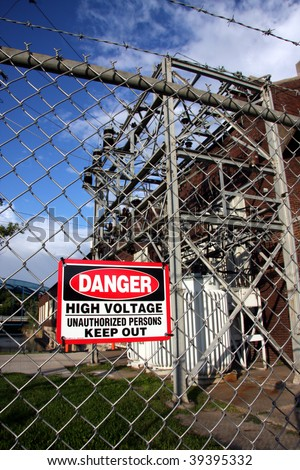 warning sign posted on the fence surrounding large electrical transformers. - stock photo