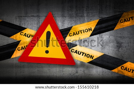 Warning sign with exclamation mark on striped caution tape - stock photo