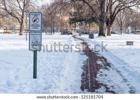 Warning signs along a park sidewalk winter - stock photo