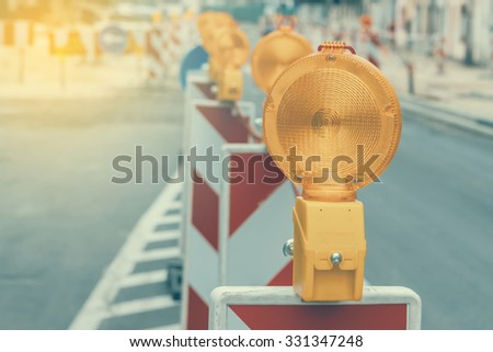 Warning signs for work in progress on road under construction. Vintage and retro style and shallow dof - stock photo
