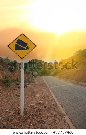 warning steep road sign slope and truck on hill.selective focus.soft focus the field for background.
