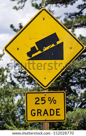 warning steep road sign with 25 percent grade and truck on hill - stock photo