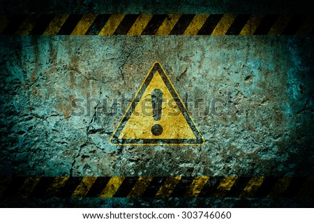 Warning symbol on dirty wall background with grunge and vignette tone - stock photo
