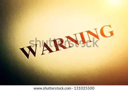 Warning text in yellow light. Macro image. - stock photo