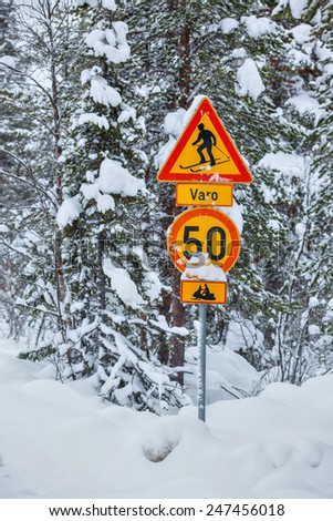 Warning traffic sign, warning skier and snowmobile sign on snowy arctic winter forest. Vertical view - stock photo