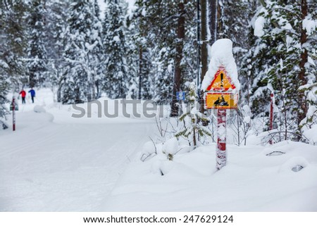 Warning traffic sign, warning skier sign on snowy arctic winter forest - stock photo