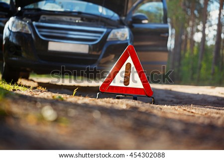 Warning triangle behind a broken down car. Selective Focus on red triangle warning sign.