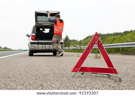Warning triangle behind a broken down car with the bonnet open on the emergency lane of a highway