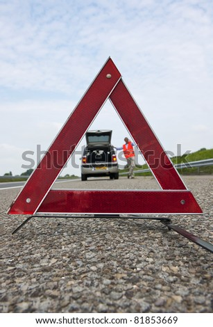 Warning triangle, with a broken down car and a man calling for assistance, out of focus in the background