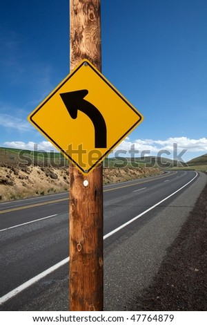 Warning turn left traffic sign on electric wooden pole winding road on background - stock photo