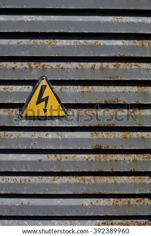 Warning voltage icon on a rusted structure