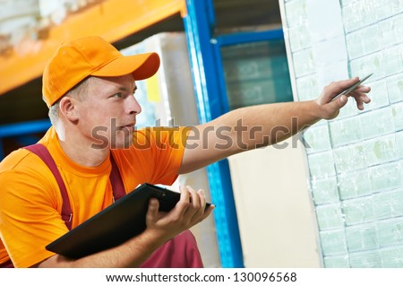 warrehouse worker man checking rack arrangement of laminate flooring - stock photo