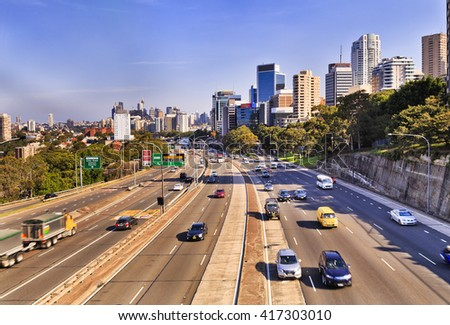 Warringah freeway endless lanes going through North Sydney from Sydney CBD, Bridge and modern skyscrapers. Blurred cars in both directions on a bright sunny day.