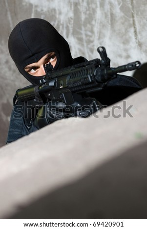 Warrior in black camouflage targeting with automatic rifle