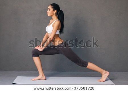 Warrior. Side view of beautiful young African woman in sportswear practicing yoga on exercise mat against grey background - stock photo
