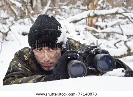 warrior with binoculars on position.Ambush.commando.warrior in the winter forest.military action. - stock photo