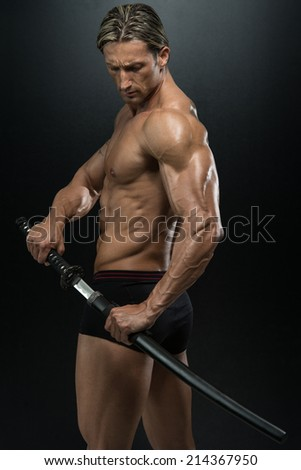 Warrior With Long Sword Over Black Background - Portrait Of A Handsome Muscular Ancient Warrior With A Sword - stock photo