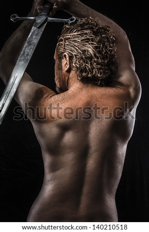 Warrior with sword, Dream, Anger, Dreaming, man covered in mud, naked, in profile, dirty skin - stock photo