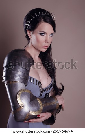 Warrior woman. Fantasy fashion idea. beautiful girl in armor.  Portrait of a beautiful lady warrior, dark-haired girl in a gray dress. bright makeup, hairstyle, spikes - stock photo