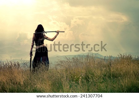 Warrior woman with sunrise clouds in the background - stock photo
