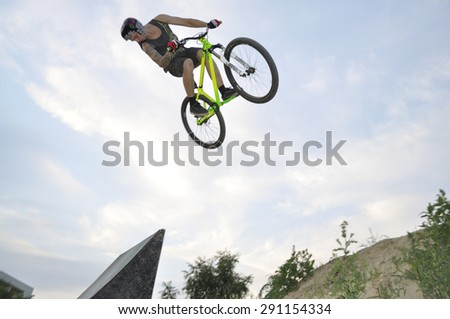 WARSAW - June 24: BMX acrobatic rider flies through the air on a bike, during local Dirt jumping game, without an audience, on the outskirts of housing estate, on June 24, 2012 in Warsaw, Poland. - stock photo