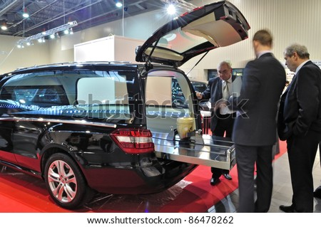 "WARSAW - NOVEMBER 20: Presentation of the urn placed in a hearse at the exhibition of funeral industry ""V Funeral Fair MEMENTO'2010"" on November 20, 2010 in Warsaw, Poland. - stock photo"