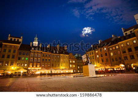 Warsaw old town marketplace square at night dusk with fountain and evening cafe and color houses - stock photo