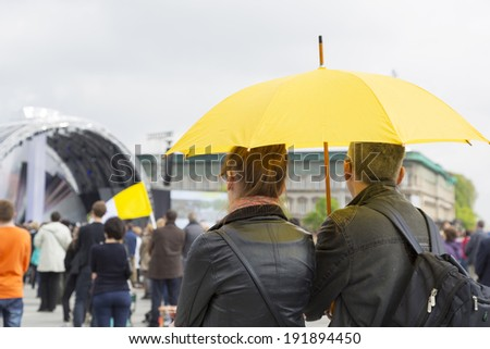 WARSAW, POLAND - APRIL 27: Couple with a yellow umbrella watching transmission of canonization mass of Pope John Paul II at the Pilsudzki Square in Warsaw on April 27, 2014.