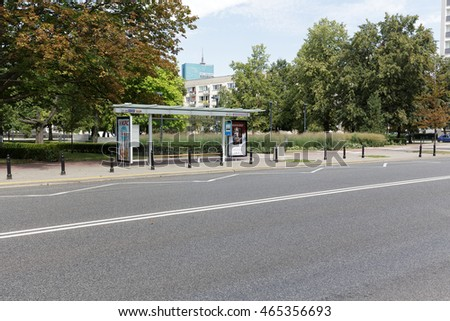 WARSAW, POLAND - AUGUST 05, 2016: General view towards a street and a covered bus stop where two billboards are placed. This bus stop is empty and waits for passengers or a bus