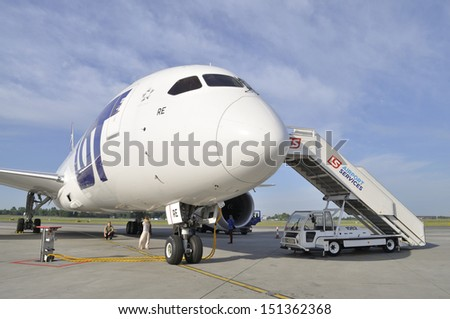 WARSAW, POLAND - AUGUST 4: Passengers under the fuselage Boeing 787 Dreamliner while preparing the aircraft LOT Polish Airlines for departure at Chopin Airport on August 4, 2013 in Warsaw, Poland. - stock photo