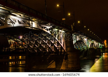 WARSAW, POLAND - DECEMBER 29: Night view of Poniatowski bridge on December 29, 2013 with National Stadium in the background. The 506m long steel bridge, designed and constructed in the years 1904-1914