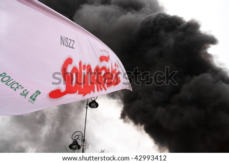 WARSAW, POLAND - DECEMBER 15: Solidarity flag and smoke from burning tires during anti government Solidarity demonstration on December 15, 2009 in Warsaw, Poland. - stock photo