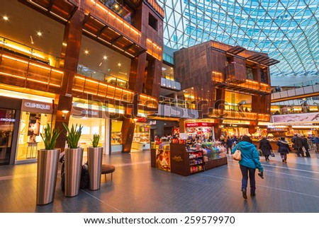 WARSAW, POLAND - 28 FEBRUARY 2014: Interior of the Zlote Tarasy shopping centre in Warsaw, Poland. The total area of the building amounts to 205 000 squere meters with over 200 shops and restaurants. - stock photo