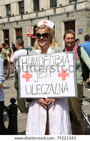 "WARSAW, POLAND - JUNE 11: An unidentified girl holds a sign that says ""Homophobia is curable"" while she takes part in the 2011 Pride Parade to support gay rights, on June 11, 2011 in Warsaw, Poland."