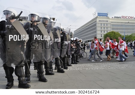 WARSAW, POLAND - JUNE 12, 2012 - Police troops protecting a route march of Russian fans towards the stadium during the Euro 2012 soccer championship Group A match between Poland and Russia. - stock photo
