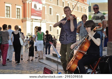 WARSAW, POLAND - JUNE 28, 2009: Street musicians perform at Warsaw's Old Town. - stock photo