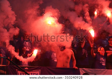 WARSAW, POLAND - MAY 02, 2015: Lech Poznan ultra supporters burn flares during Polish Cup Final football match between Legia Warsaw and Lech Poznan at the National Stadium in Warsaw. - stock photo