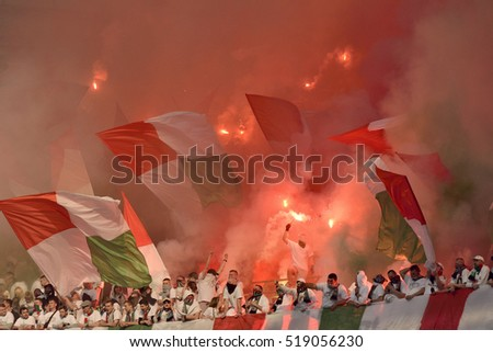 WARSAW, POLAND - MAY 2, 2016. Legia Warsaw fan stand at PGE Narodowy stadium in Warsaw, during Polish Cup Final Legia Warszawa vs Lech Poznan, with people, Legia flags, burning fireworks.