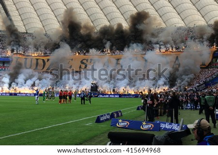 WARSAW, POLAND - MAY 2, 2016: Legia Warsaw fanatical fans lighting smioke flares during Polish Cup final football match between Legia Warszawa and Lech Poznan at the National Stadium in Warsaw.