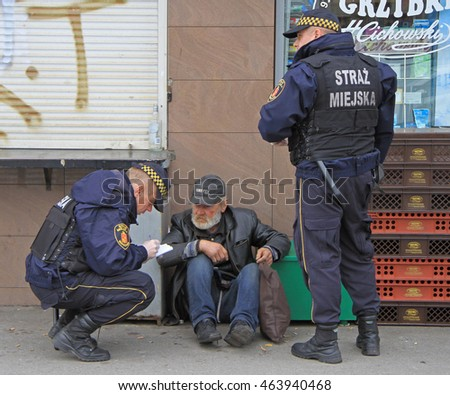 WARSAW, POLAND - OCTOBER 24, 2015: police officers are checking some strange man outdoor in Warsaw, Poland
