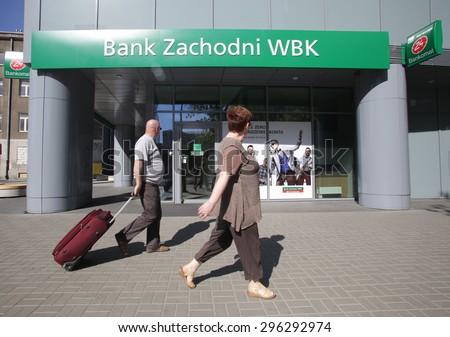WARSAW, POLAND - SATURDAY, JUNE 6, 2015: Pedestrians walk past a Bank Zachodni WBK branch. Bank Zachodni WBK (BZ WBK) is the third largest bank in Poland   - stock photo
