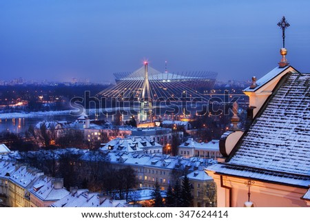 Warsaw winter evening cityscape, capital city of Poland, view towards Vistula river, Swietokrzyski Bridge and National Stadium, St Anne Church on the right