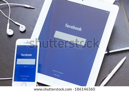 WARSZAWA, POLAND - APRIL 01, 2014: Facebook app on screen of Ipad and Iphone 5s. Facebook is the largest social network in the world. It was founded in 2004 by Mark Zuckerberg and his roommates.