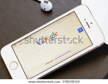 WARSZAWA, POLAND - APRIL 01, 2014. Google search page on screen of Iphone 5s.  In December 2013 Alexa listed google.com as the most visited website in the world. - stock photo