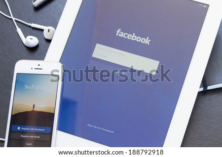 WARSZAWA, POLAND - APRIL 01, 2014: Instagram and Facebook app on screen of Ipad and Iphone 5s. Facebook is the largest social network in the world. It was founded in 2004 by Mark Zuckerberg . - stock photo