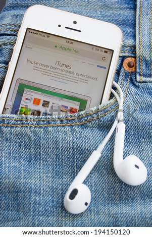 WARSZAWA, POLAND - APRIL 17, 2014: Iphone 5s in jeans pocket with Itunes page. iTunes is a media player, media library, and mobile device management application developed by Apple Inc. - stock photo