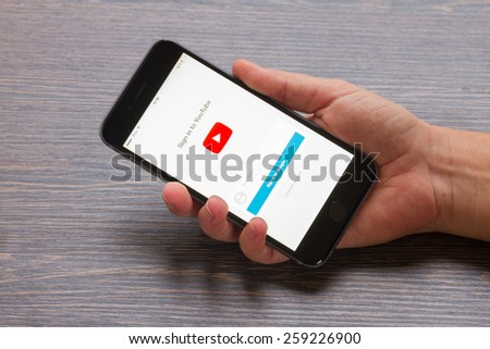 WARSZAWA, POLAND - DECEMBER 16, 2014. Hand holding new Apple Iphone 6 in gray space black color with youtube page - stock photo