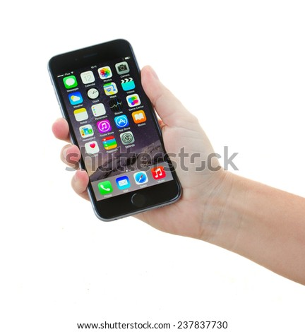 WARSZAWA, POLAND - DECEMBER 12, 2014. Hand holding New Apple  Iphone 5s in gray space color isolated on white. The iPhone is the top-selling phone of any kind in some countries. - stock photo