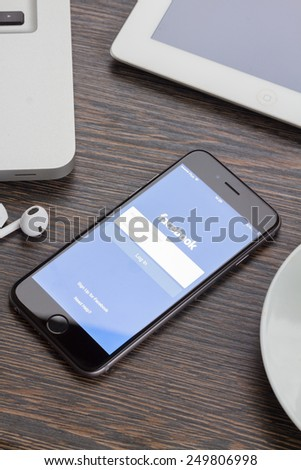 WARSZAWA, POLAND - DECEMBER 16, 2014. New Apple Iphone 6 in gray space black color with Facebook screen on working table. Facebook is one of the famous social media web site. - stock photo