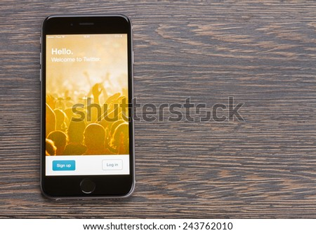 WARSZAWA, POLAND - DECEMBER 16, 2014. New Apple Iphone 6 in gray space black color with twitter page laying on wooden table.  - stock photo